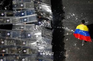 Policiais e manifestante em Caracas. Foto de Jorge Silva/Reuters