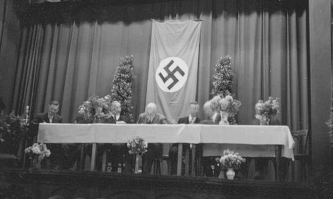"""In July 1937, the Mormon Prophet Heber J. Grant, spoke to 800 members at a rented meeting hall in Frankfurt. Like all buildings in Nazi Germany, it came with a large swastika flag. On Aug. 7, the Deseret News, the Church-owned Salt Lake City daily, ran this picture. In its news columns, the DN regularly published wire service stories about Hitler's treatment of Germany's Jews. But in the religion section, it had no qualms about associating the Church President with Nazi symbolism."" (David Clark)"