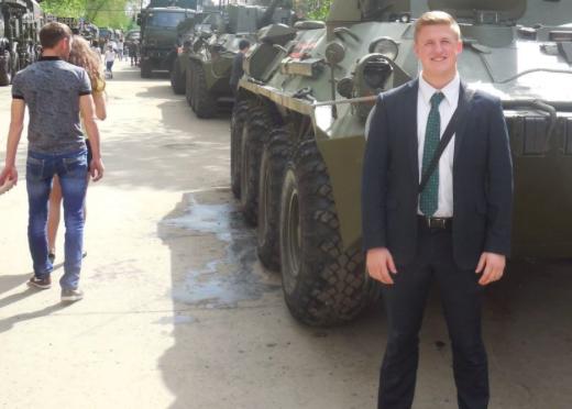 Drake Oldham, um dos 6 missionários SUD deportados da Rússia, posando em frente a um tanque de guerra. Note a ausência da costumeira plaqueta de identificação.